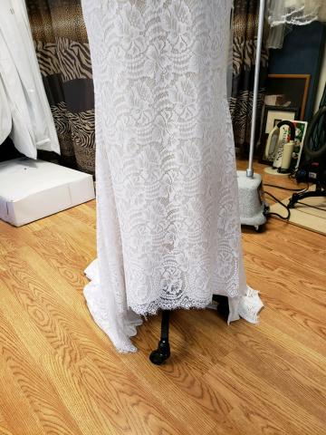 This gown could not be hemmed by removing the lace.  the gown was cut and the lace reapplied. Can you find the seam?